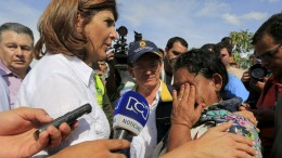 Colombia's Foreign Minister Maria Angela Holguin consoles a deported woman from Venezuela close to the border, near Villa del Rosario village